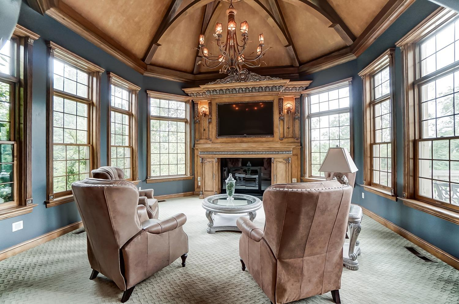 The hearth room includes an ornate fireplace with built-ins, an arched beamed ceiling and a large chandelier.