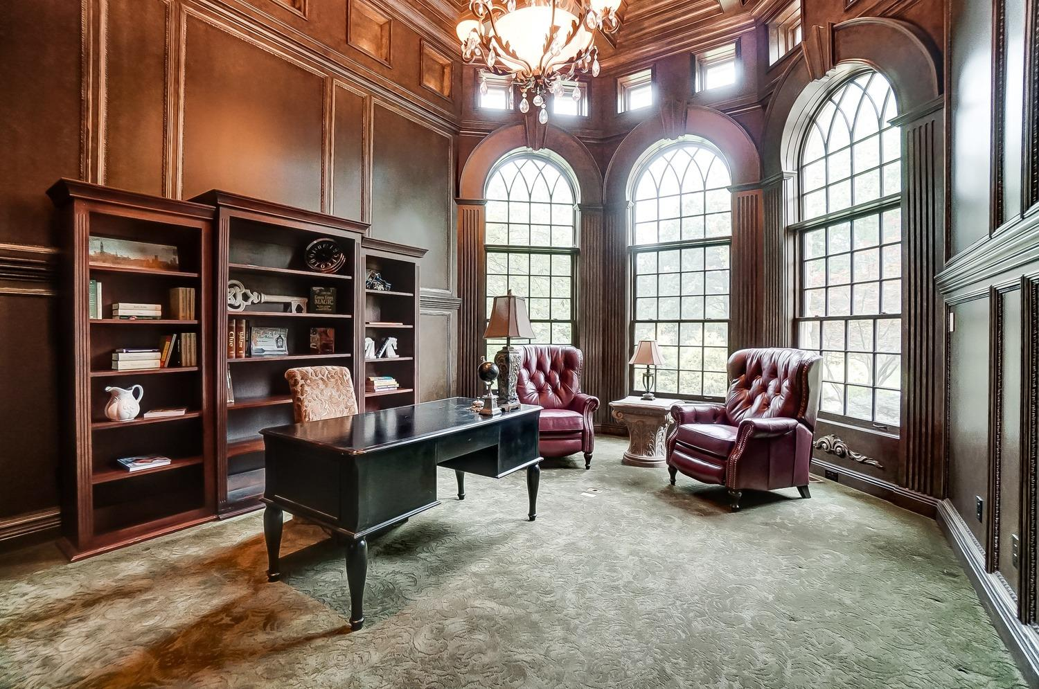 A handcrafted all-wood library with 16' high ceilings includes a fireplace with built-in bookshelves.