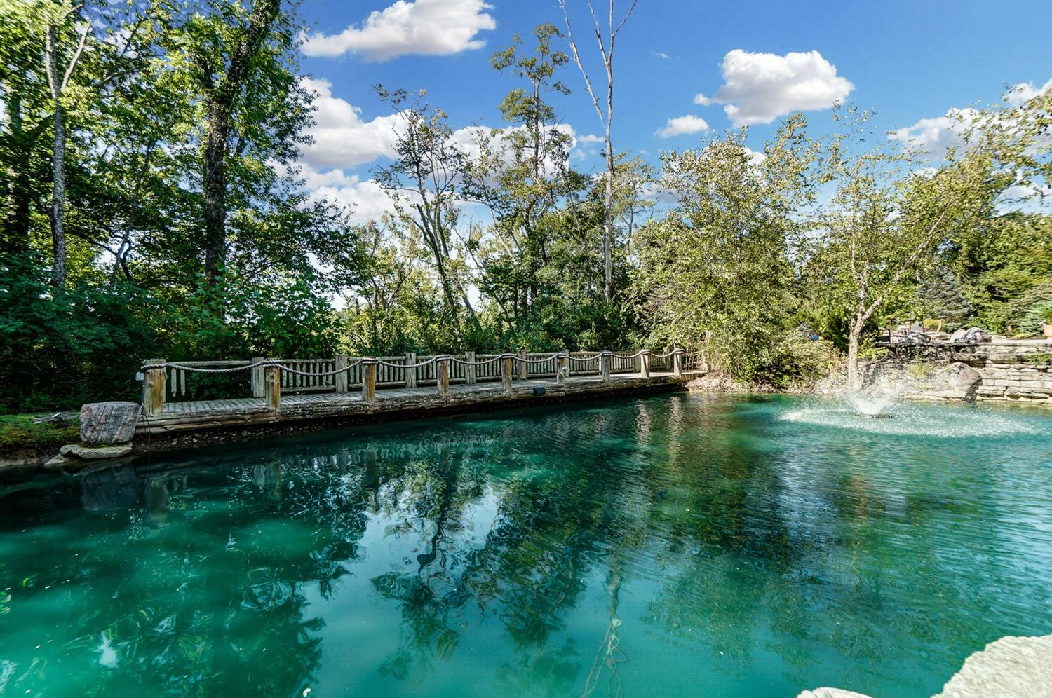 There is a stocked pond with a wood bridge/dock that connects the pool deck area to a private wooded retreat complete with a firepit.