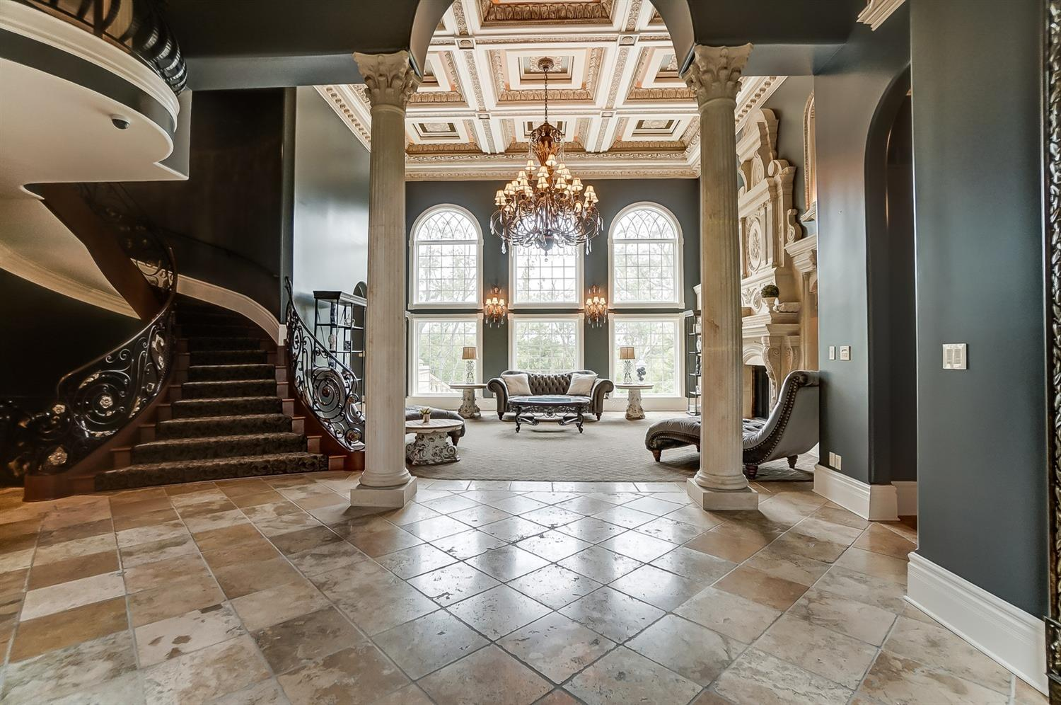 The living room boasts 22' high ceilings with beamed and recessed ceiling detail trimmed with ornate plaster moldings and an imported chandelier.