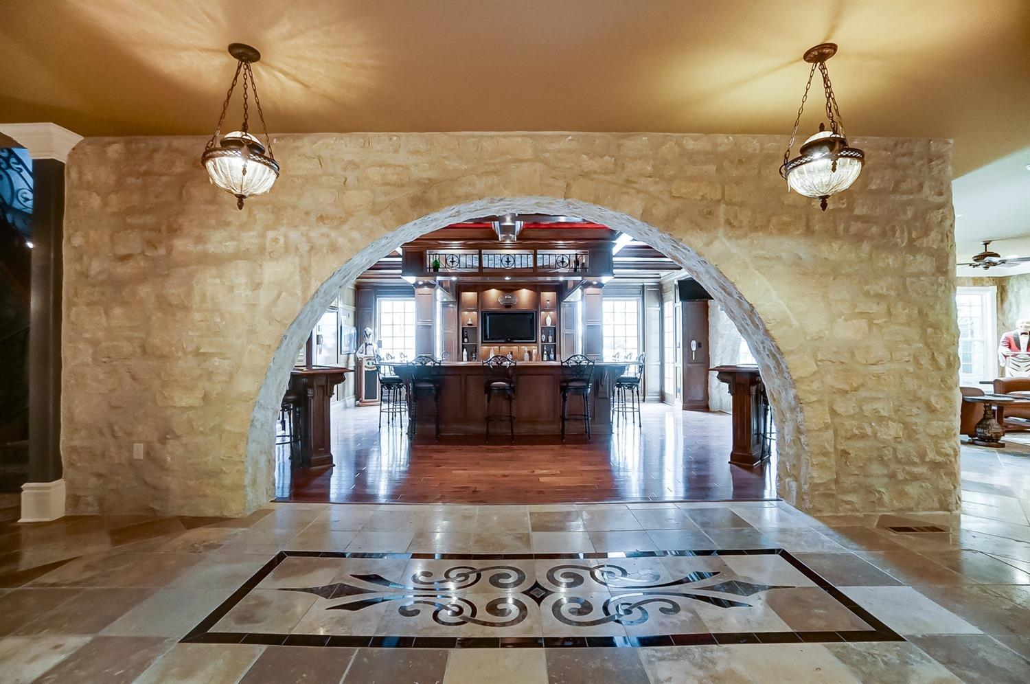 The home boasts a full-size Old World tavern with large arched stone entryways.