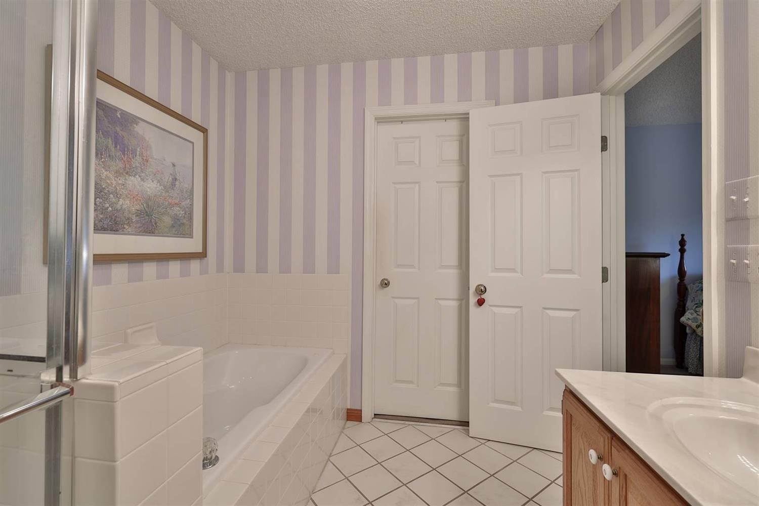 Master bath - walk-in closet next to jetted tub.