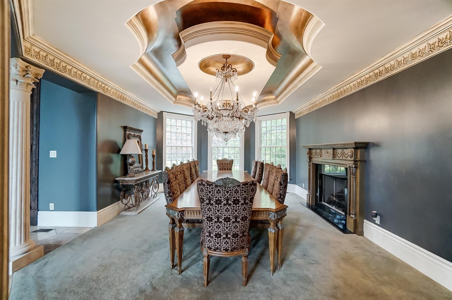 The formal dining room boasts a tray ceiling, ornate moldings, two chandeliers and a fireplace.