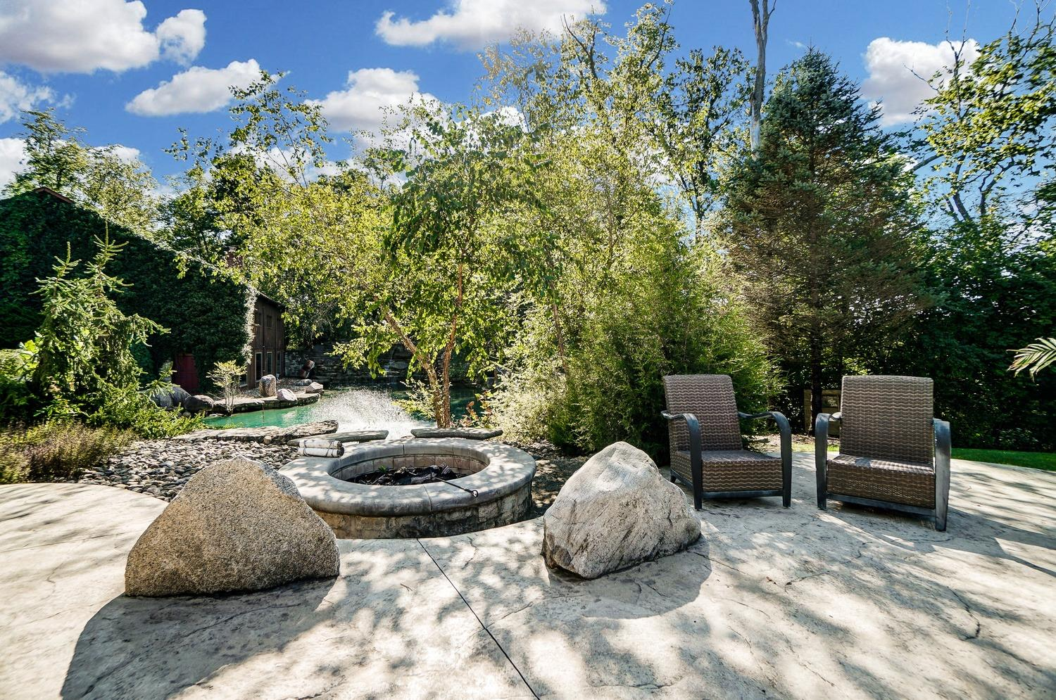 There is a large built-in firepit with a gas log lighter situated next to the pool patio with views of the pool and scenic waterfall pond.