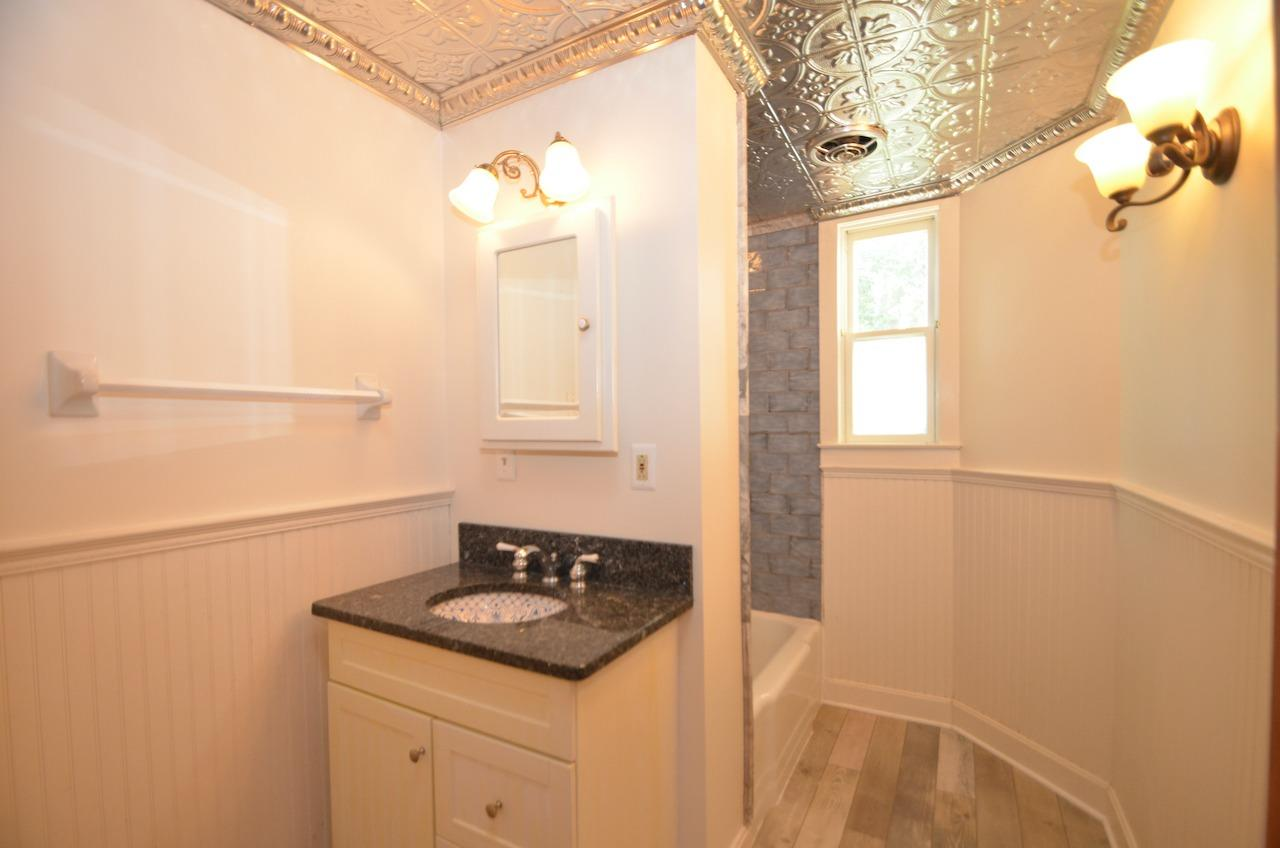 Updated (in a vintage style) hall bath.  Behind the wall is a mid (20th) century square soaking tub, with newly installed vintage inspired tile and tin ceiling.  Serene and lovely.