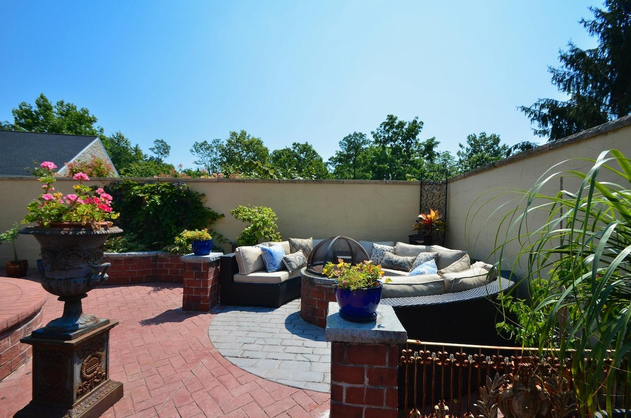 this corner of the pool deck has room for circular sofa conversation area around a gas powered firepit.