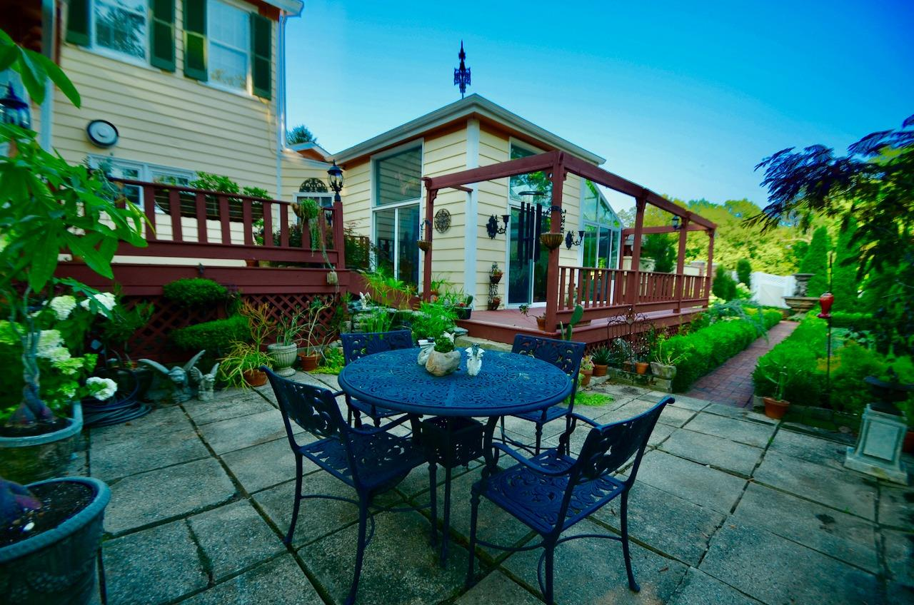Around the side of the house is another nice patio area and some extensive decking accessed from the solarium, greenhouse and breakfast room.  The waterfall/fountain is on the other side of the table by the deck.