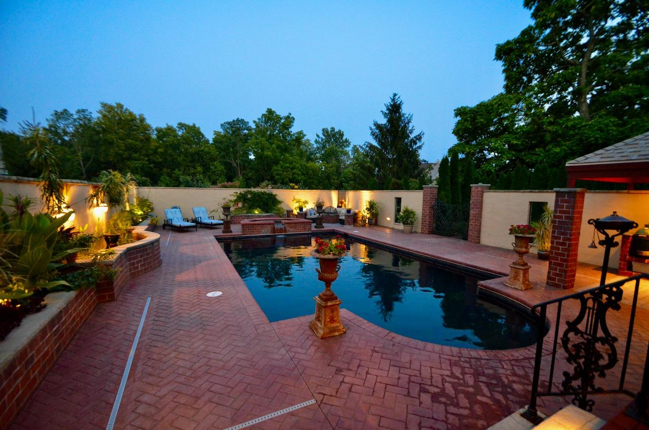 The custom crafted concrete decking was designed to look like brick that was there for decades; The 6 ft. stucco privacy wall was constructed to mimic the private courtyards in New Orleans (and to provide privacy from neighboring homes). The wall even houses a koi pond here to the left. It all came together to create a lush and welcoming getaway environment.