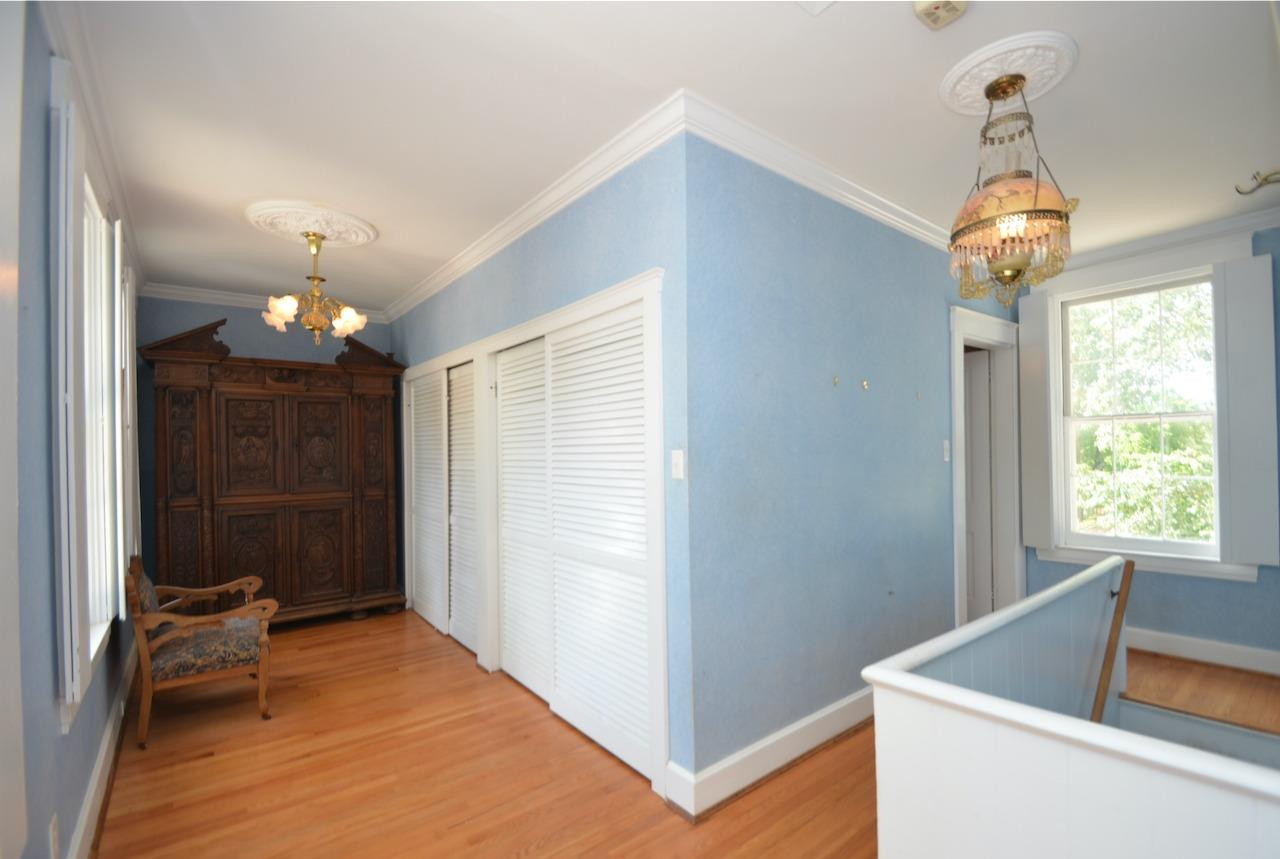 This is the dressing room portion of the primary suite.  To the right, you will see the rear stairway that goes directly from the hall between the dining room & the kitchen to the bedroom, leading us to believe this rear portion of the suite may have originally been a maid's room.  The door near the window at the top of the stairs is to the master bath.