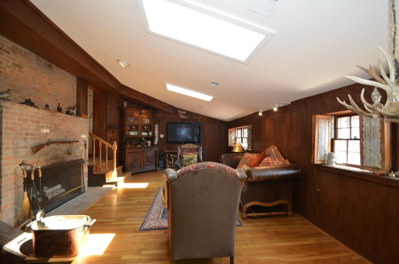 Just 4 steps down from the kitchen is this family room with vaulted ceiling.  Perhaps a mid (20th) century addition?  It's light and bright with the skylights, but still warm and cozy with the large wood burning fireplace and PECKY CYPRESS walls.
