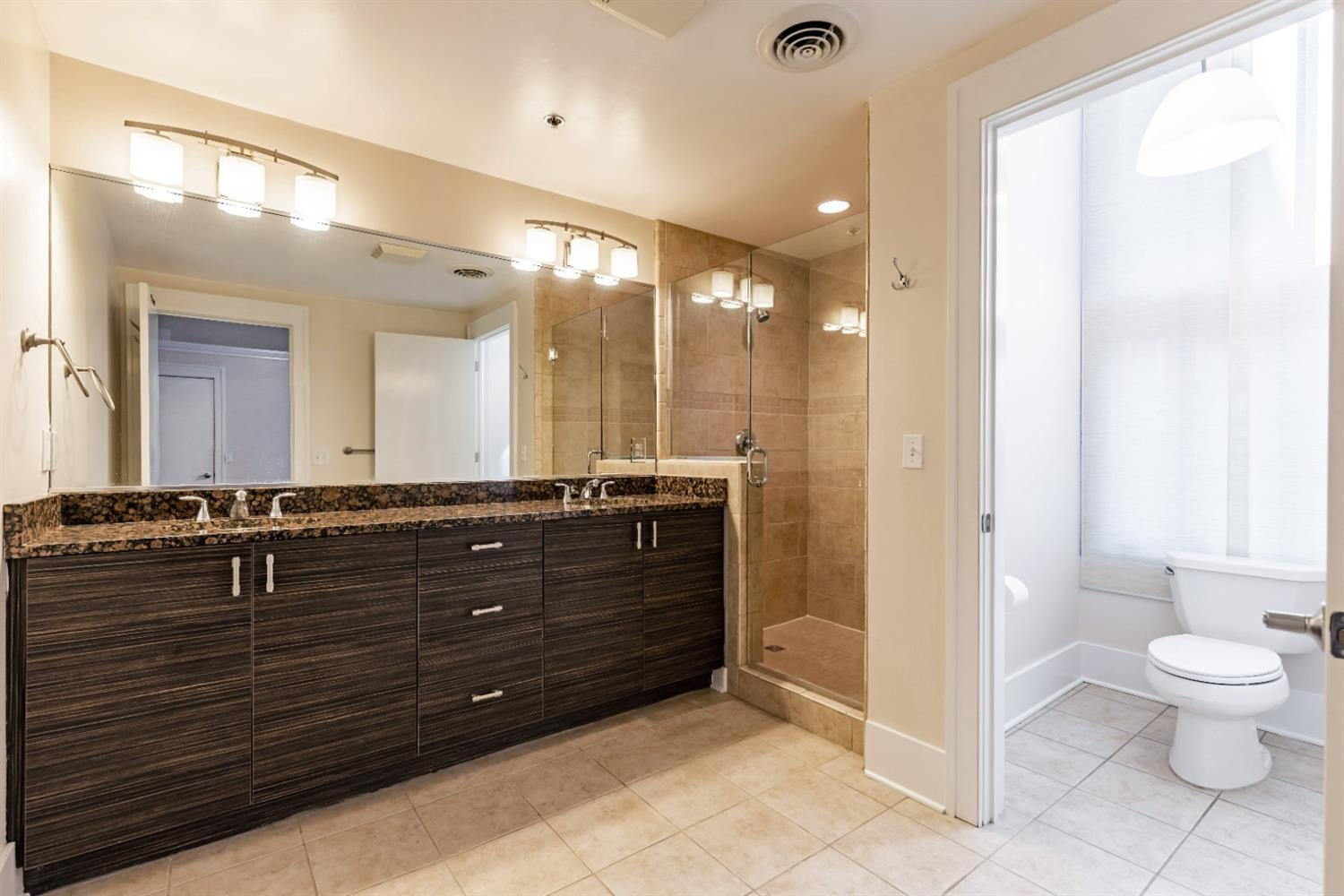 Spacious master suite with stunning zebra wood cabinetry, granite counters and spacious walk-in shower, separate water closet.