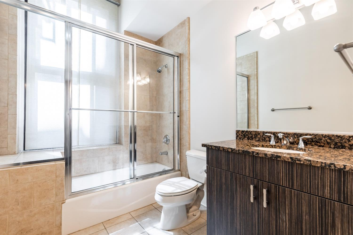 Guest bath with spacious full tub. Beautiful zebra wood cabinetry with granite counters.