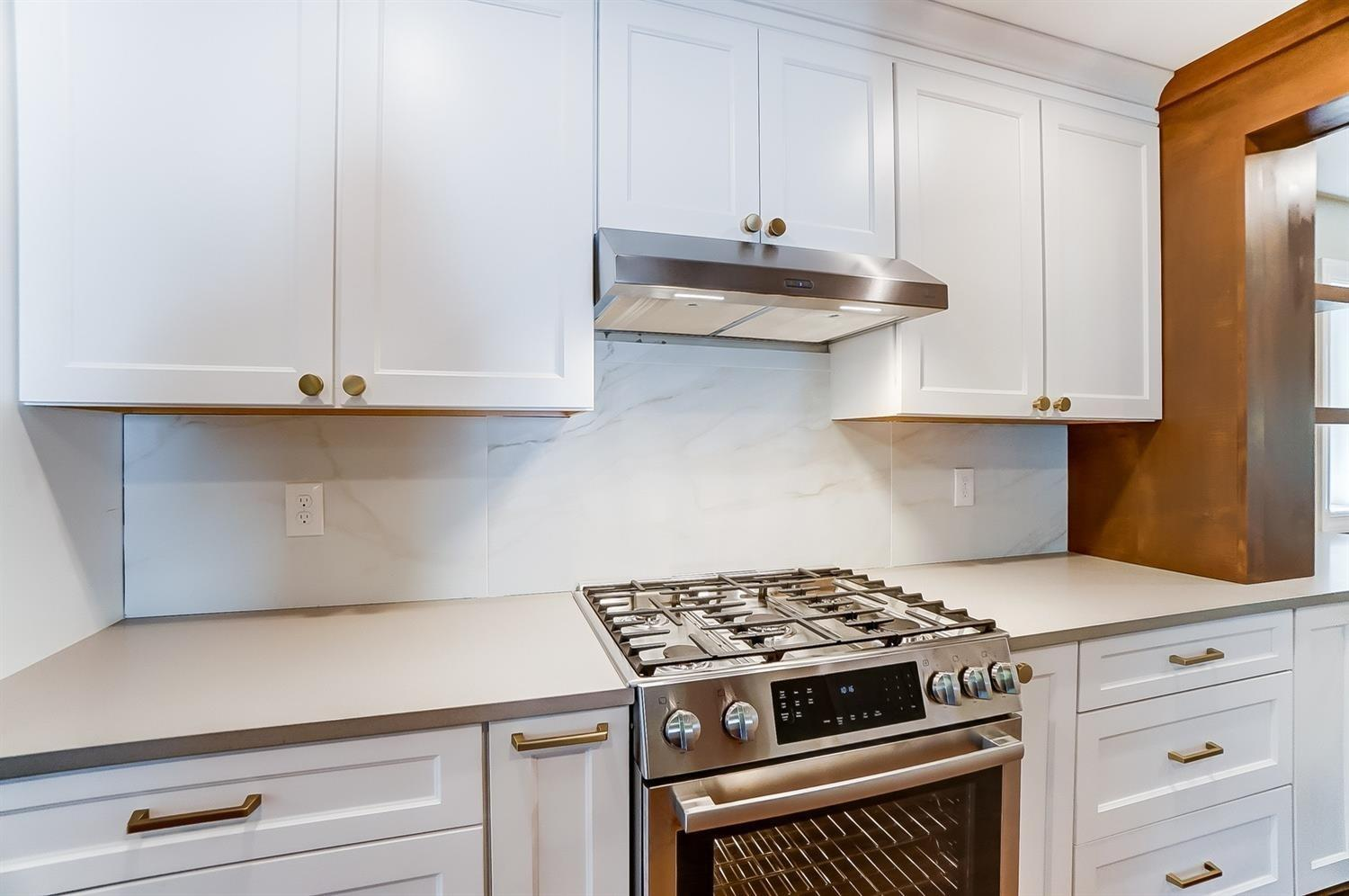 Gleaming Bosch appliances throughout this kitchen. Gas 5 burner range/oven. Quartz mixed recycled solid surface counters have flecks of mica that offer sparkle.