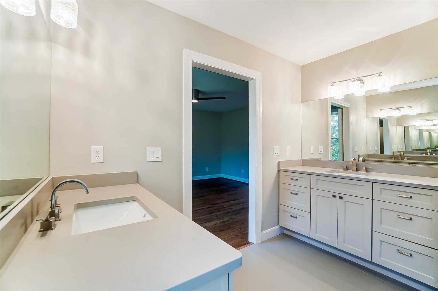 2nd floor, Owner's Bath, dual vanities, ample cabinets, bright crystal lighting, tile floor. Window lets in natural light. Light and airy definitely describes this space well.