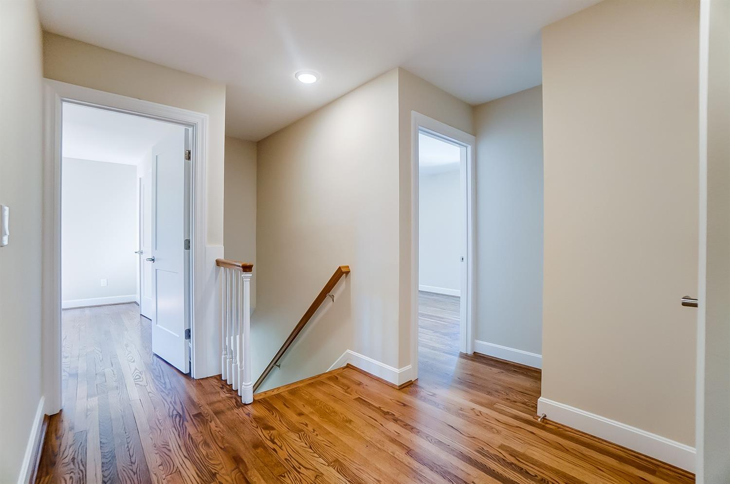 2nd floor hallway is generously sized and offers opportunity for a seating area. Gleaming hardwood floors and LED lighting give this area lots of open, light and airy feeling. Hallway closet handle seen to right. Front bedroom with ensuite bath is at left, two more bedrooms to right have shared bath.