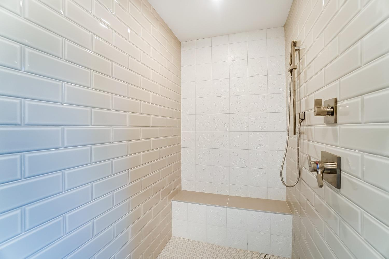 2nd floor, Owner's Suite, additional view of fabulous shower. Willow/Bamboo relief tile and beveled dove gray subway tile. Bench seat. Rain showerhead in ceiling, premium Kohler fixtures with added spray head visible.