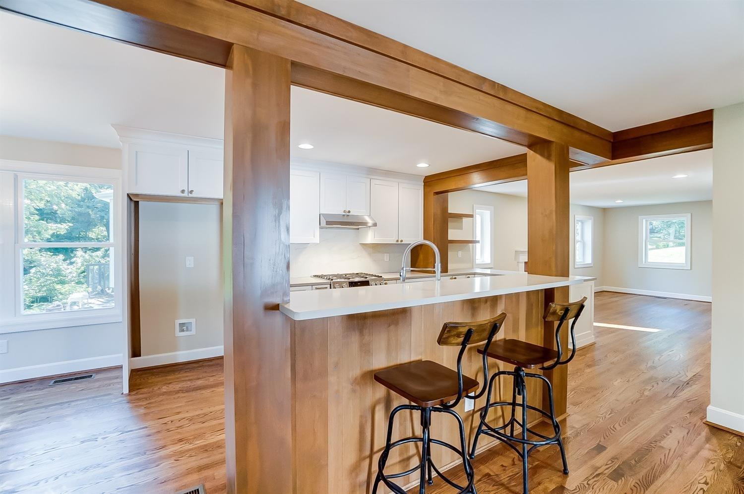 1st floor, kitchen view from back of home with breakfast bar visible. Beams artfully provide structural support while keeping a sense of modern farmhouse at play here.