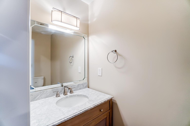 1st floor half bath. Pocket door saves space. Marble counter, mixed metals, beveled glass mirror.