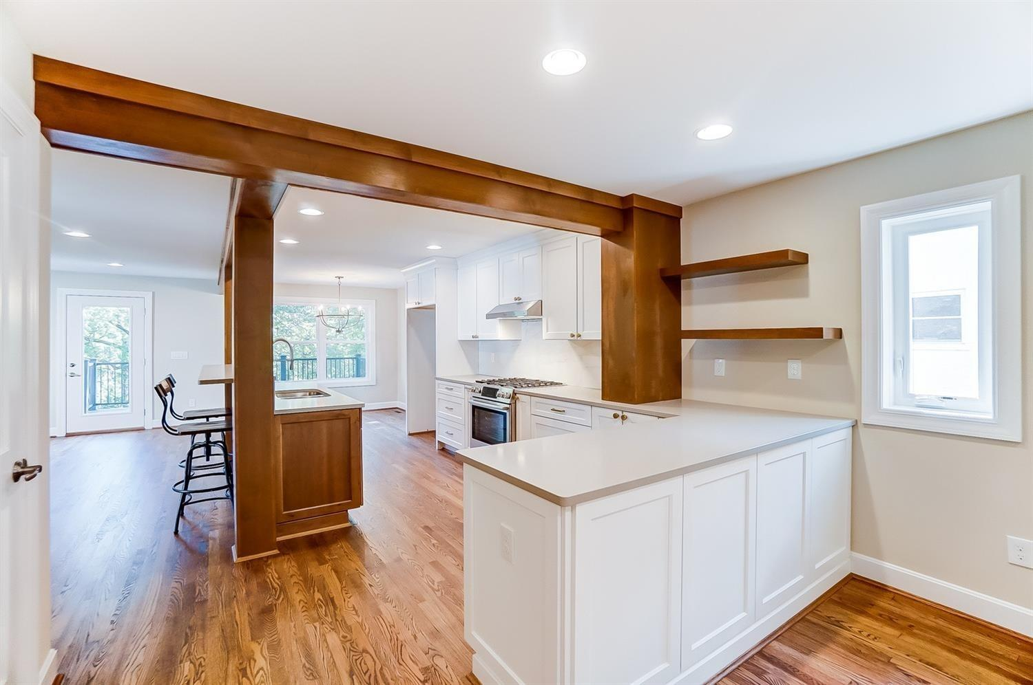 1st floor, kitchen alternate view. Wood beams allow visualization of end of original 1950 home and artfully provide important structural support.