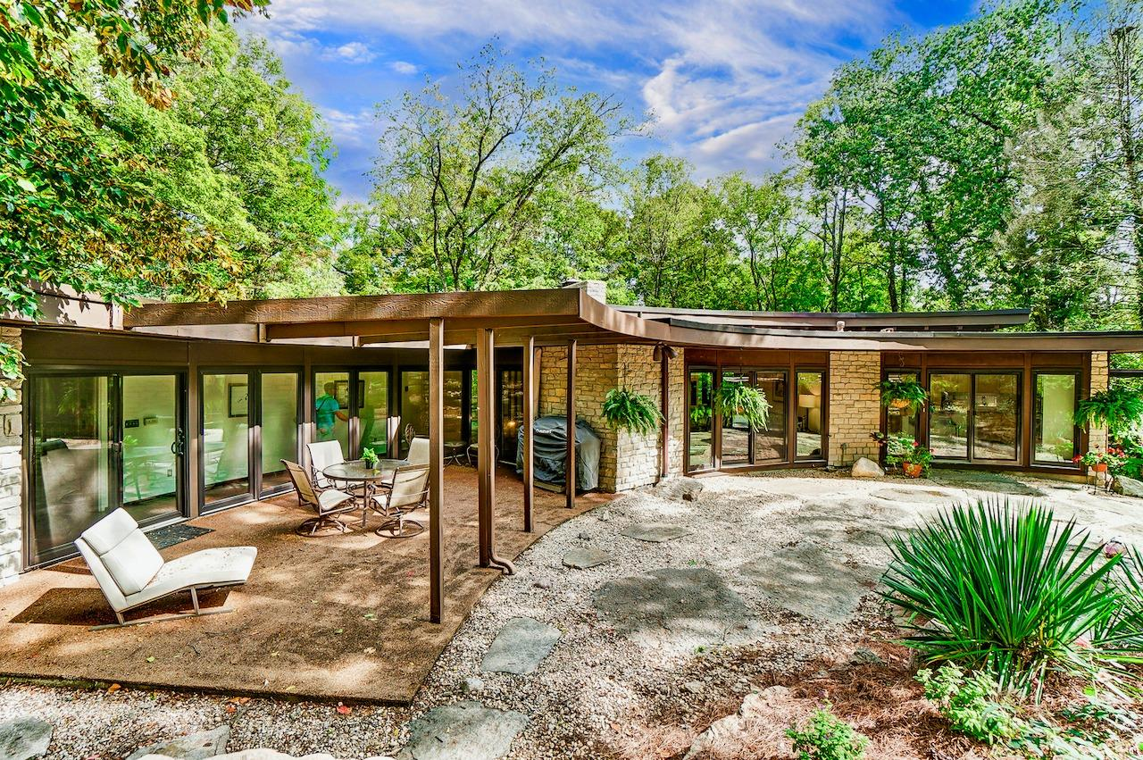 There are walkouts from nearly every room in the home to both the front and back of the semi-circle - on both levels!  This inner circle courtyard overlooks the stunning original waterfall.  Parallels to Wright's iconic Fallingwater?  You be the judge.