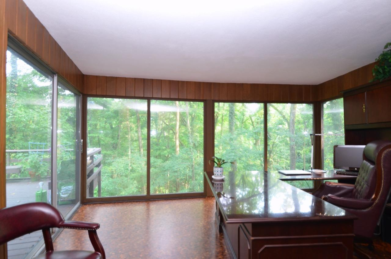 The first floor study - who knew when this home was built - long before the internet and Zoom meetings - that so many people would be working from home in 2021.  But seriously, how much work would you get done staring out into the woods and watching nature?! There is also a walkout from this room to the huge treetop deck.