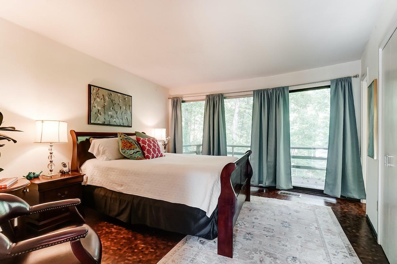 This second bedroom with en suite bath is the other bedroom on the main level (two additional bedrooms are on the lower level). This room also features walkout to deck, two closets (one with built ins, one walk in) and a full bath overlooking the woods.