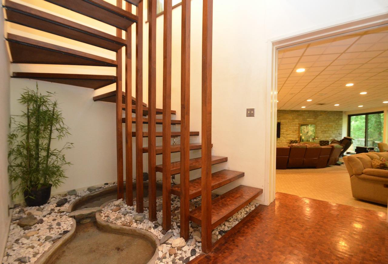 And it's not just ANY stairway - no siree - it's a stairway with original water feature! Here is a peek into perhaps the most dramatic room in the house (although it's really hard to choose), the lower level family room/ rec room.