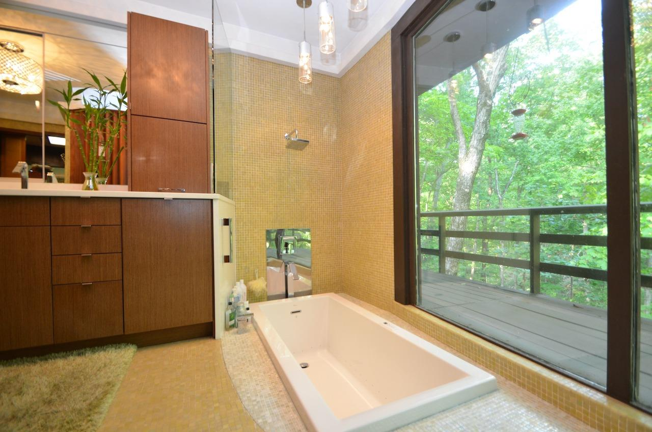 And perhaps best of all, the custom garage door cabinet to the left of the shower that conceals the coffee maker!  The glass mosaic tile is original (who knew glass mosaics would be all the rage 50+ years after this house was built), and the cabinetry, plumbing, sinks, quartz counters and bubble tub have all been updated to match the original.  Not shown behind the camera is a sunken planter in front of the window, just because.