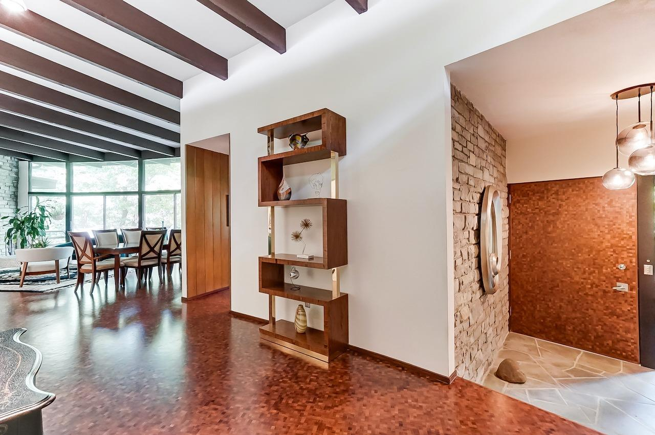 The walnut floors are a real show stopper, as are the fieldstone walls (seen here in the foyer) that repeat in several places on the inside and outside of the home. Funny how that stone look is so imitated in 2021, but never as well as it is done here.