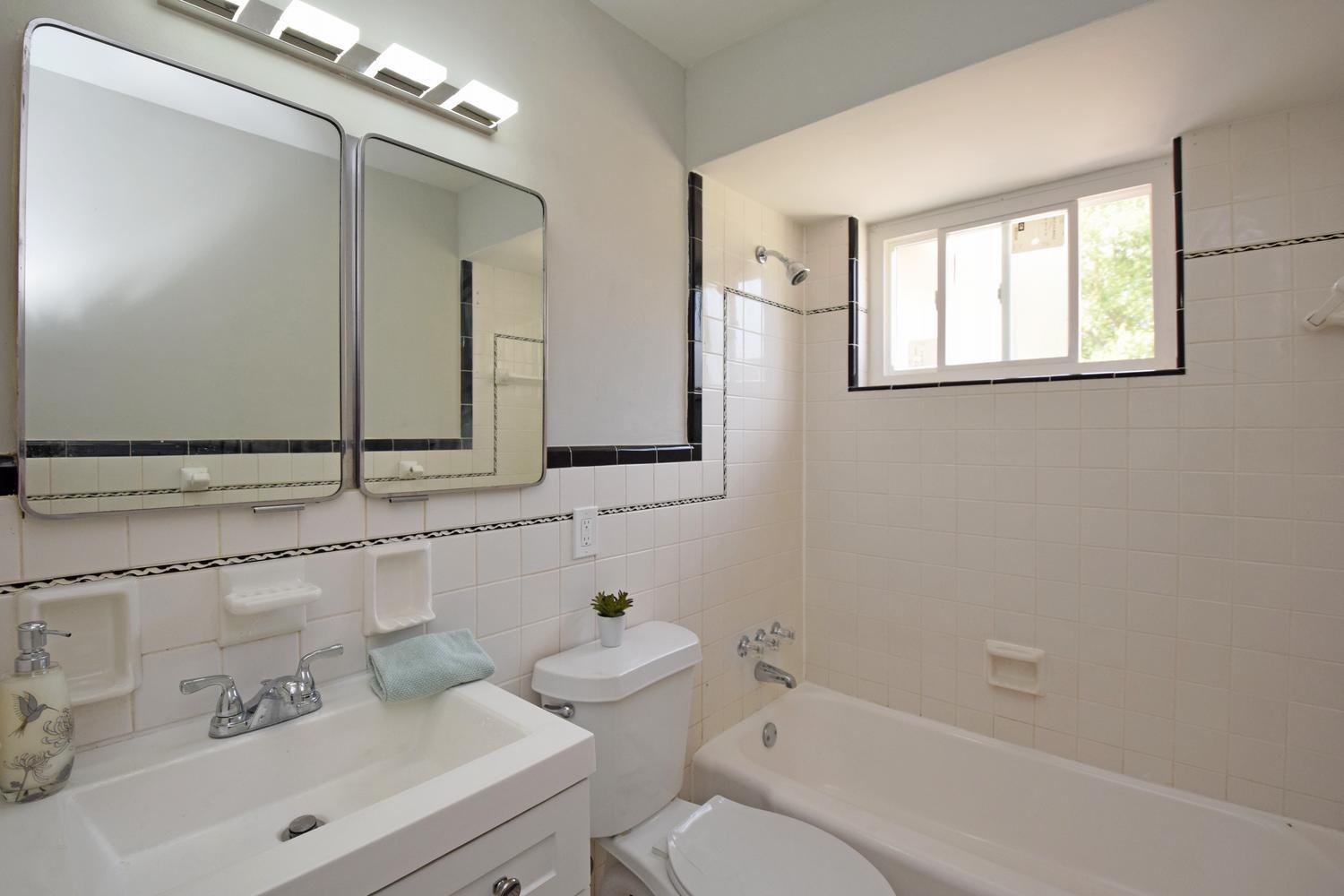 Primary Bathroom with refinished tub, new vanity, commode, Medicine Cabinets and lighting