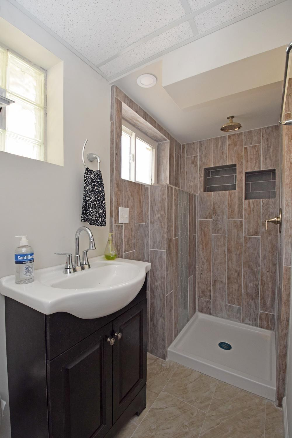 Lower Level Bathroom with new Shower, Vanity, Commode and Flooring