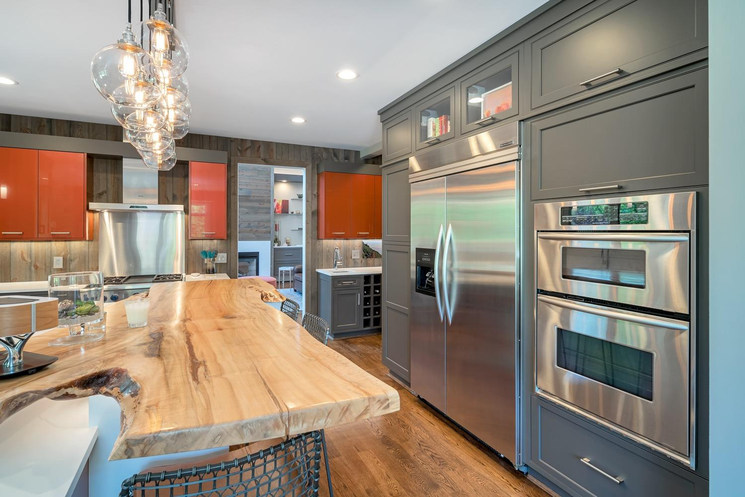 """Kitchen island with Cambria quartz countertop with """"living edge"""" 8 ft Ambrosias Maple bar (yeah…it's that cool). Kitchen with oversized Kitchen Aid refrigerator and separate double oven with convection oven/microwave."""