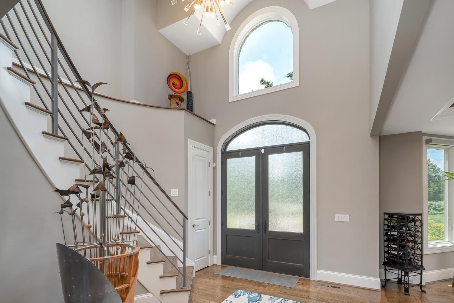 Entry features vaulted ceilings, hardwood floors, a double door with transom, and a coat closet.