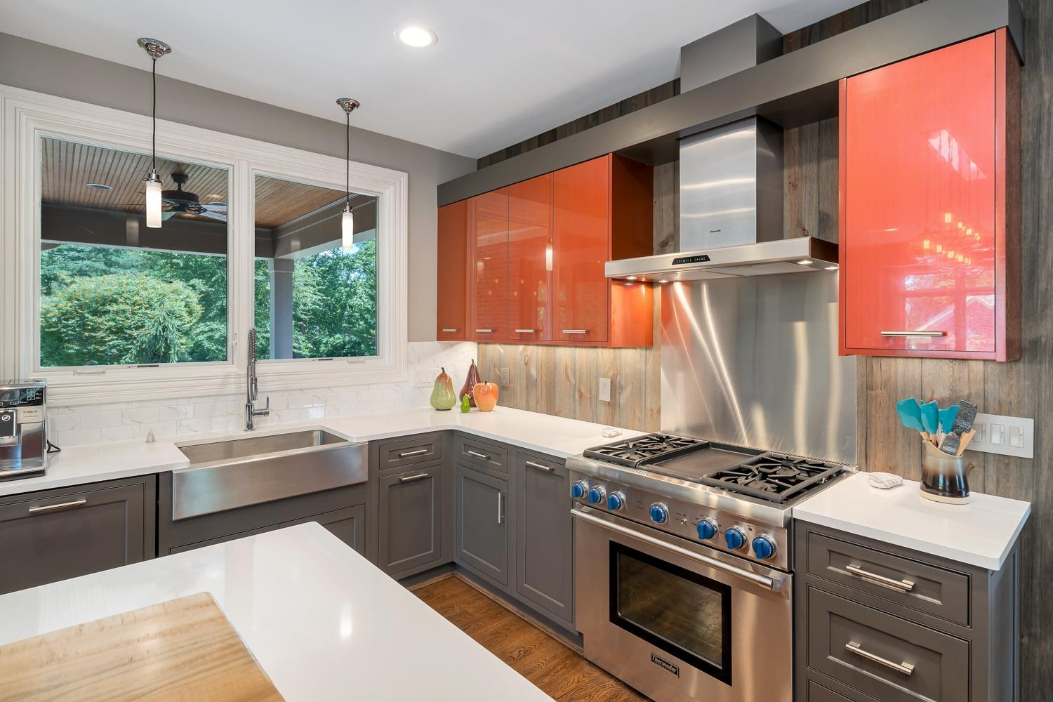 Kitchen features Thermador range with griddle, LED lighting under cabinets, and oversized windows above sink.