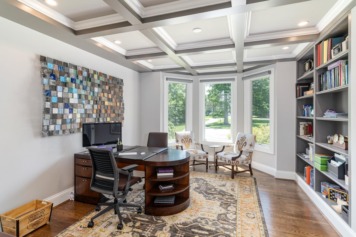 Study adjacent to first floor master with coffered ceiling, hardwood floors, bay window, built-in bookshelves, and motorized Hunter Douglas blinds.