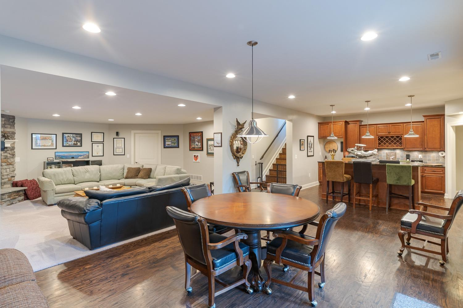 Lower level gaming table area with view of family room/recreation room and wet bar.
