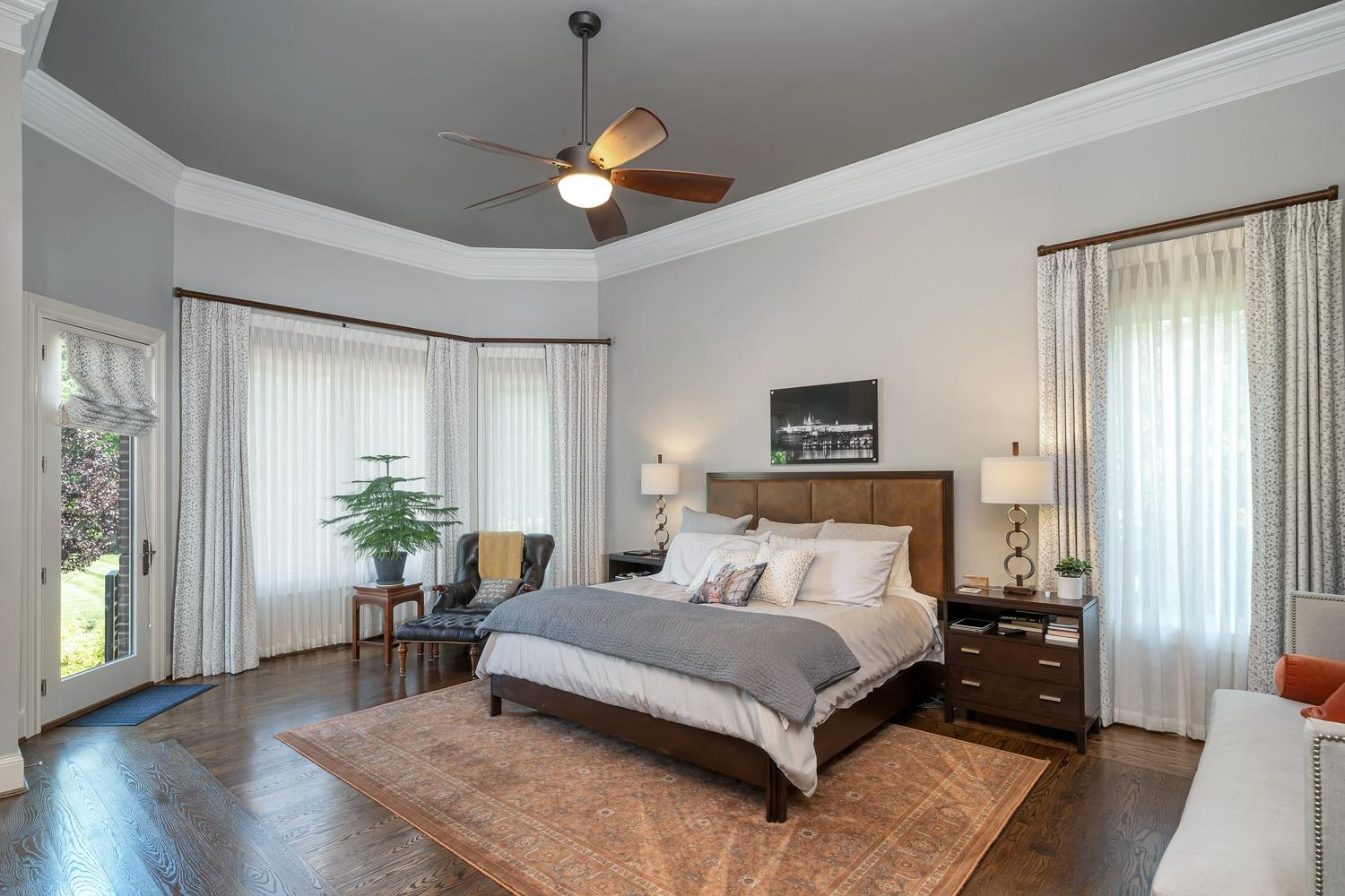 Master suite features 12' ceilings, hardwood floors, custom draperies, and SONOS powered sound system speakers.