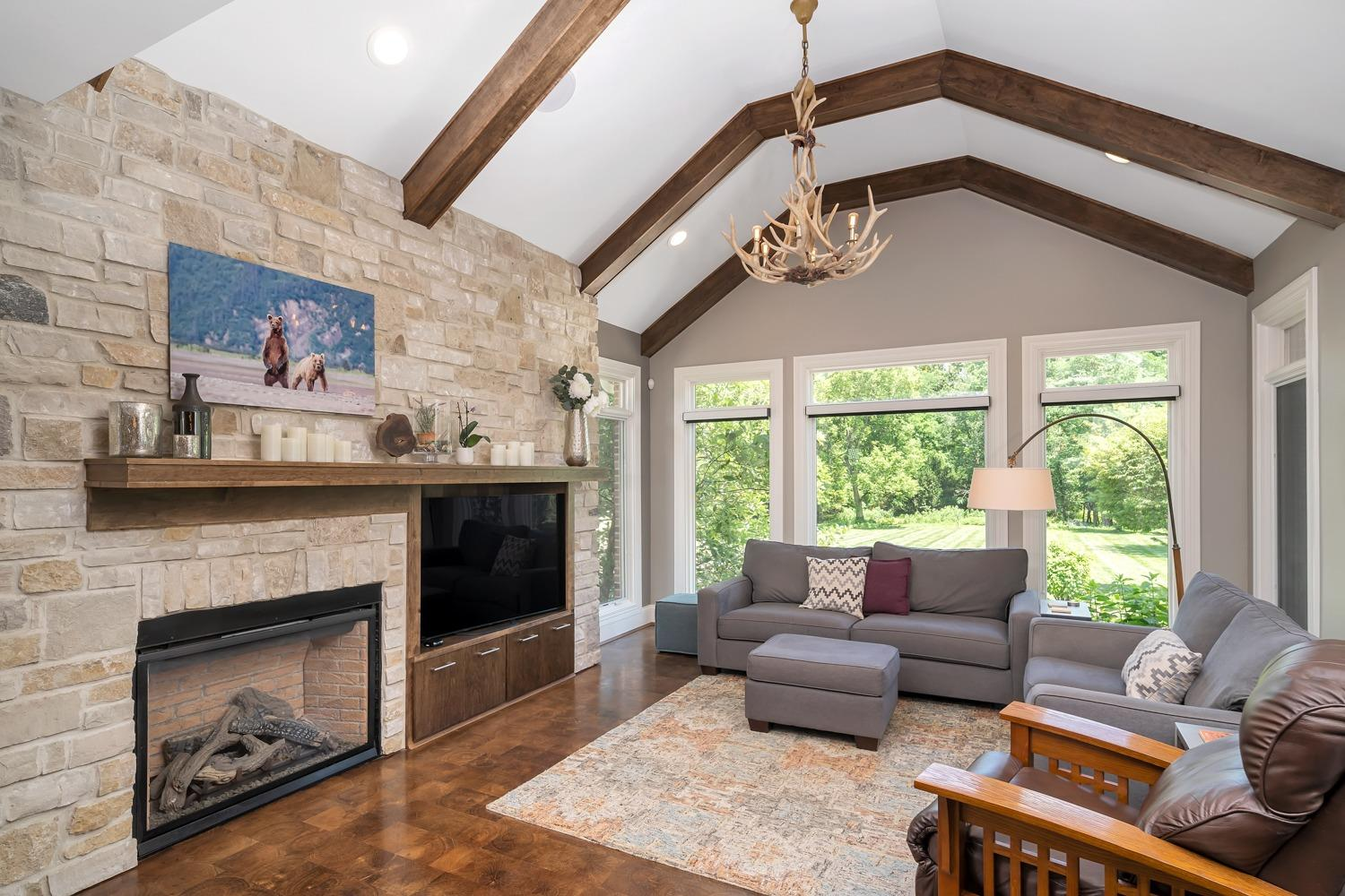 """Hearth room features vaulted ceiling with custom wood beams, a stone fireplace (gas), and custom wood built-ins (mantel, storage, and tv space). Did you notice the specialty """"end cut"""" flooring and the """"antilier"""" (alright… my name for an antler chandelier)?"""