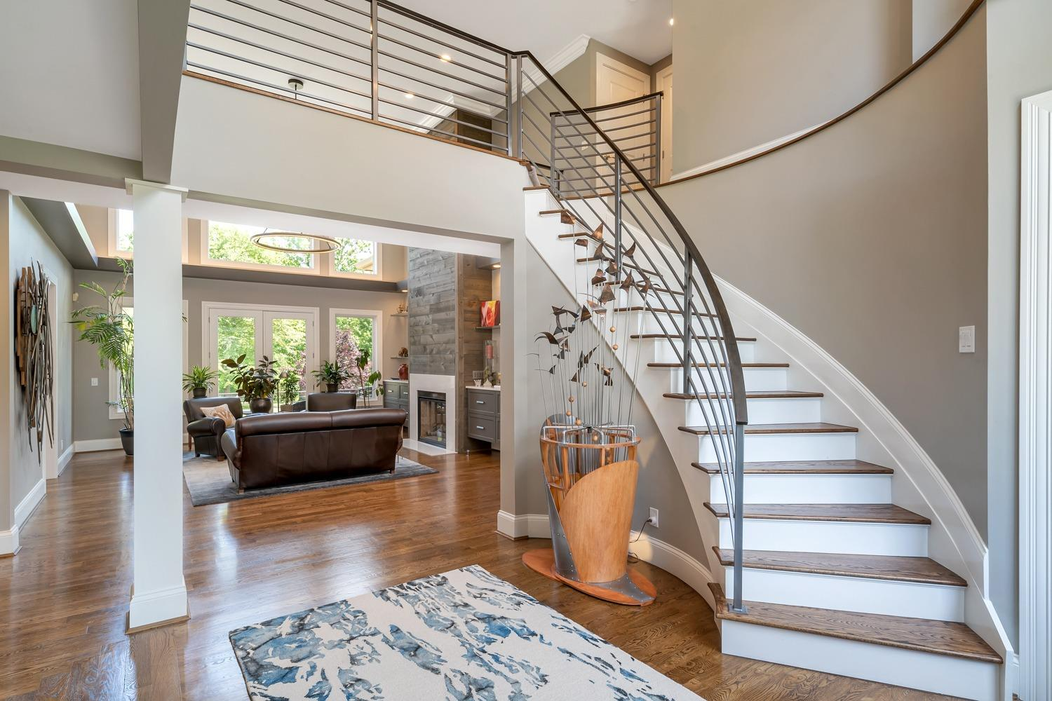 Entry features curved staircase and custom railings by Elegant Iron.