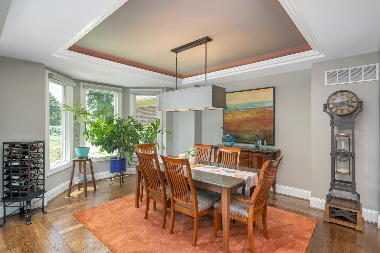 Dining area features tray ceiling, hardwood floors, bay windows, upscale lighting, and is perfect for entertaining guests.