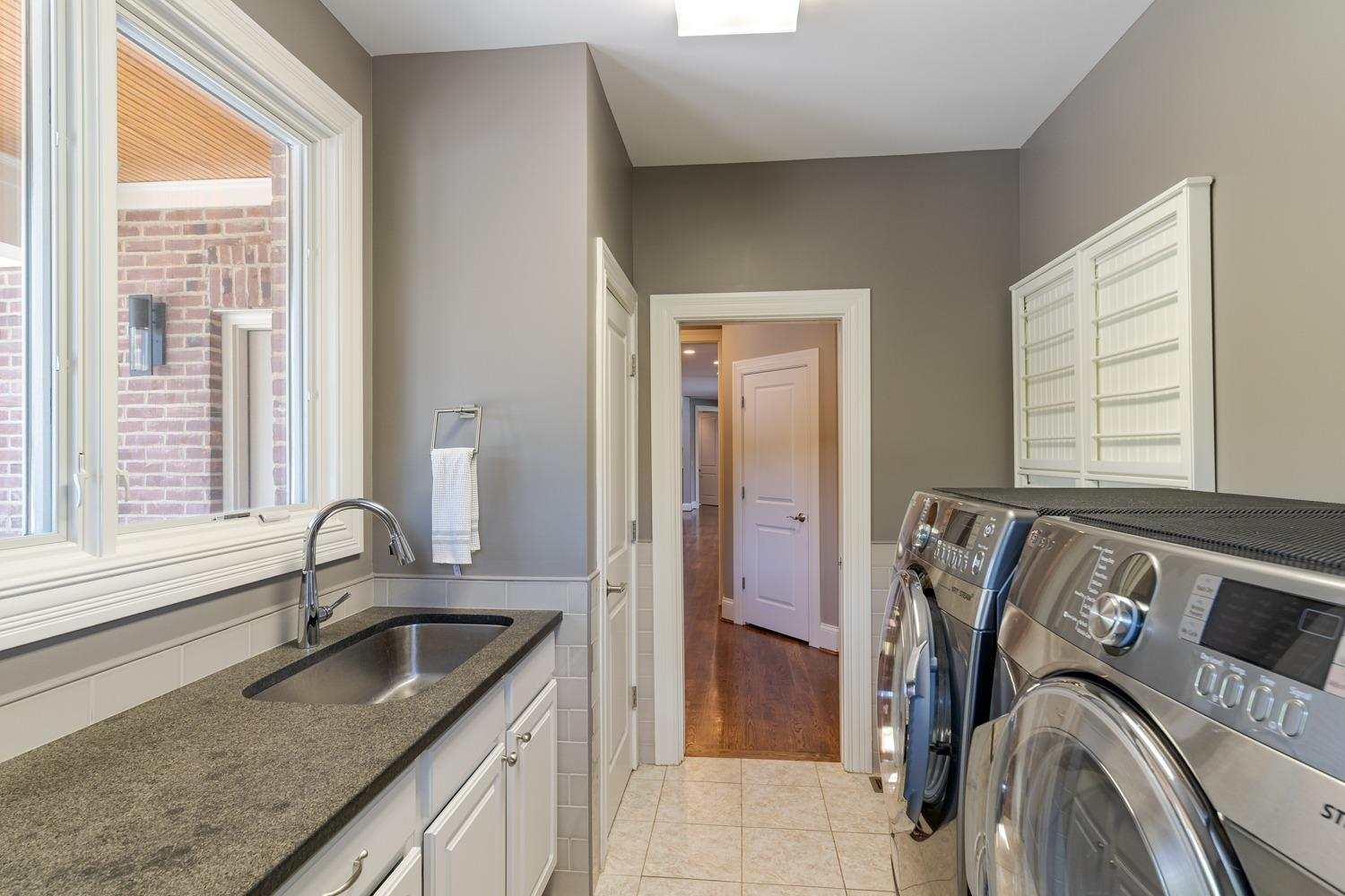 Laundry located on first floor with ample counter space, supply closet, and retractable drying rack.
