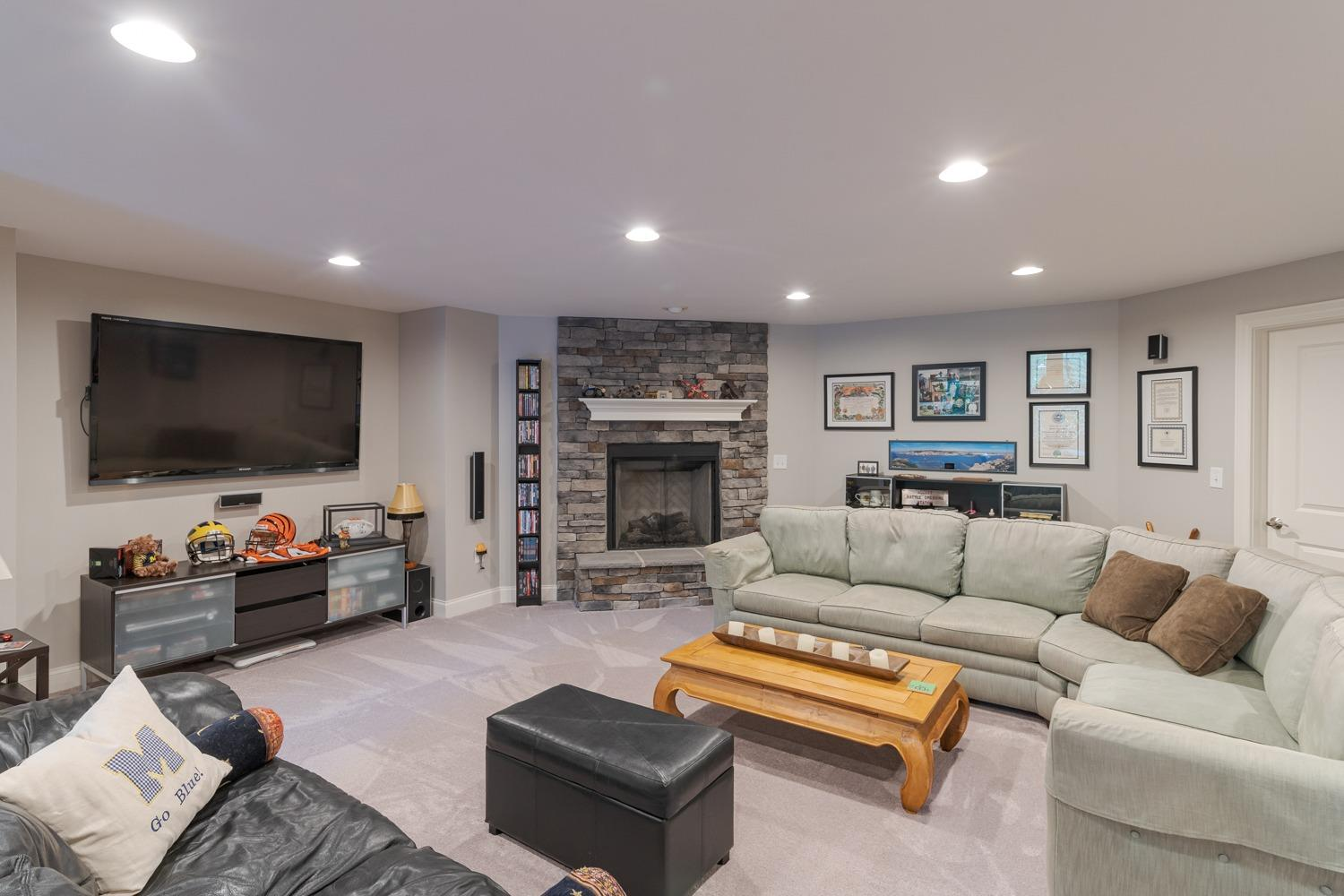Lower level family room/recreation room features wall-to-wall carpet, recessed lighting, and stone fireplace (gas).