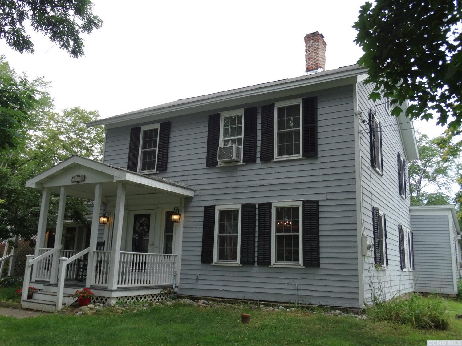 This incredibly maintained, circa 1800 colonial farmhouse was owned by a Vanderbilt family. President Martin Van Buren once stayed here. Enjoy the lovely, updated country kitchen with wide plank wood floors and a wood burning stove. The library has built-in shelves and a decorative fireplace. The formal dining room has a beautiful chandelier, ornate details and fireplace is ready for entertaining. The finished attic has a bedroom and sitting room. Be creative in the indoor 1st floor workshop. Relax on the huge wrap around covered deck, overlooking the cleared and wooded yard, with 3 outbuildings on 4 acres. Newer Pella windows, a new 1,000 gallons fiberglass septic tank and new 2nd floor bathroom. Hot tub and some furniture are available fo