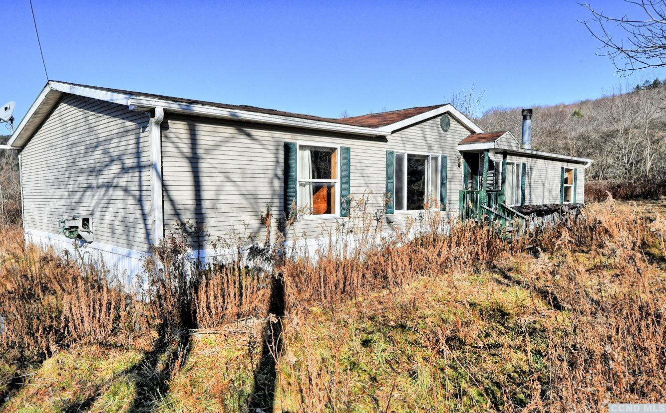 A 3 to 4 Bedroom, 2 Bath Spacious Double Wide Manufactured Home on 3 Acres! The home features an eat-in kitchen with a center island, a dining room with a pellet stove, a family room with a fireplace, a living room, an additional room for an office or a 4th bedroom, a laundry room, a covered rear deck, and a 1 1/2 car heated garage. The knotty pine walls offer a warm and cozy ambience. The home has a nice setting with beautiful views. A Nice Home in a Beautiful Setting!