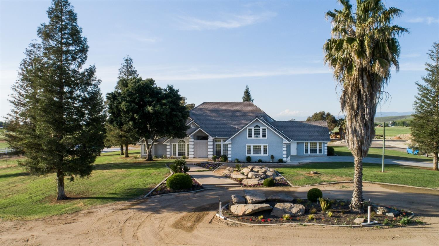 This one-owner custom home on 20 acres is a must-see. The 4,000+ sq. ft. home has 3 bedrooms on one side and two bedrooms on the other (with its own entrance) making it a perfect setup for a large family, multi-generational living, or home-based business. The large room above the garage would be an ideal game room or a 6th bedroom. The paid solar makes this home very inexpensive to maintain. The 7000 sq. ft. shop is wired with 3-phase power and has large roll-up doors on each end of the main center area, as well as plenty of work area on both the north and south sides with many sliding doors for easy access. The north side was designed with ease of converting it to stalls in mind. The property has water rights from the Enterprise Canal with pipes in place for irrigating the entire parcel. The back pasture is fenced for horses and has a year-round pond. Schedule your appointment to view this property today!