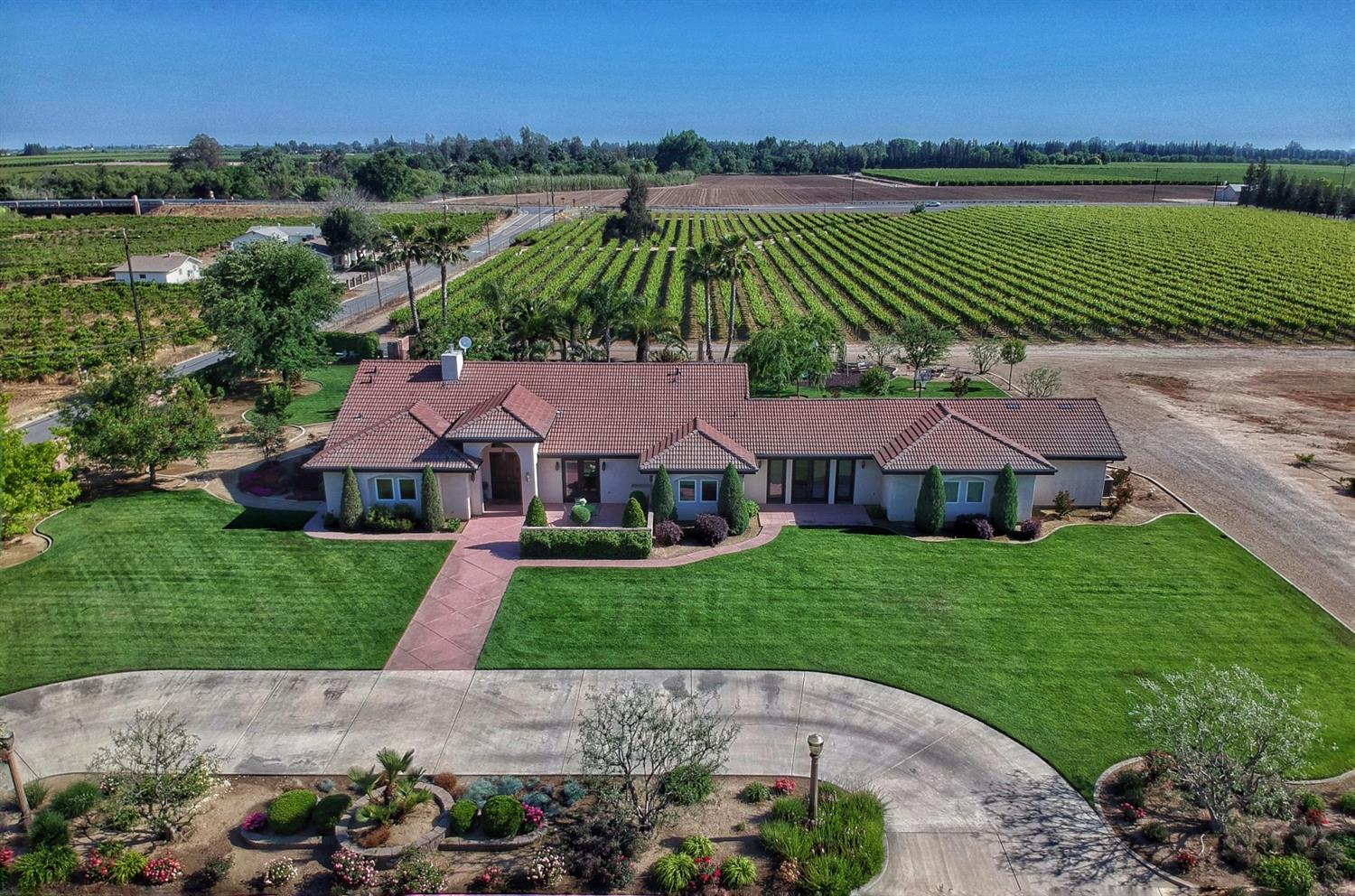 Stunning vineyard estate in Clay School District! Lovingly cared for by the original owners, this home shines with pride of ownership. Entering the home, you'll be greeted by a barreled-ceiling entry way, beautiful hardwood floors, and towering vaulted ceilings with authentic wood beams. A chef's kitchen opens to the family room and includes custom cabinetry, a center island, a gas cooktop and granite counter tops. The master suite is a true retreat with french doors to the patio and a luxurious bathroom that includes a large spa tub, spacious shower, dual sinks and a vanity space. Three additional bedrooms, 2 additional bathrooms, an office, and a game room complete the floor plan. Paradise can be found in the backyard with the sparkling pool and roomy patio area. The grounds feature manicured landscaping, a family orchard, OWNED solar, and a second home site that has been county approved (per seller). Just over 15 fully fenced acres, most of which is planted to Scarlet table grapes.