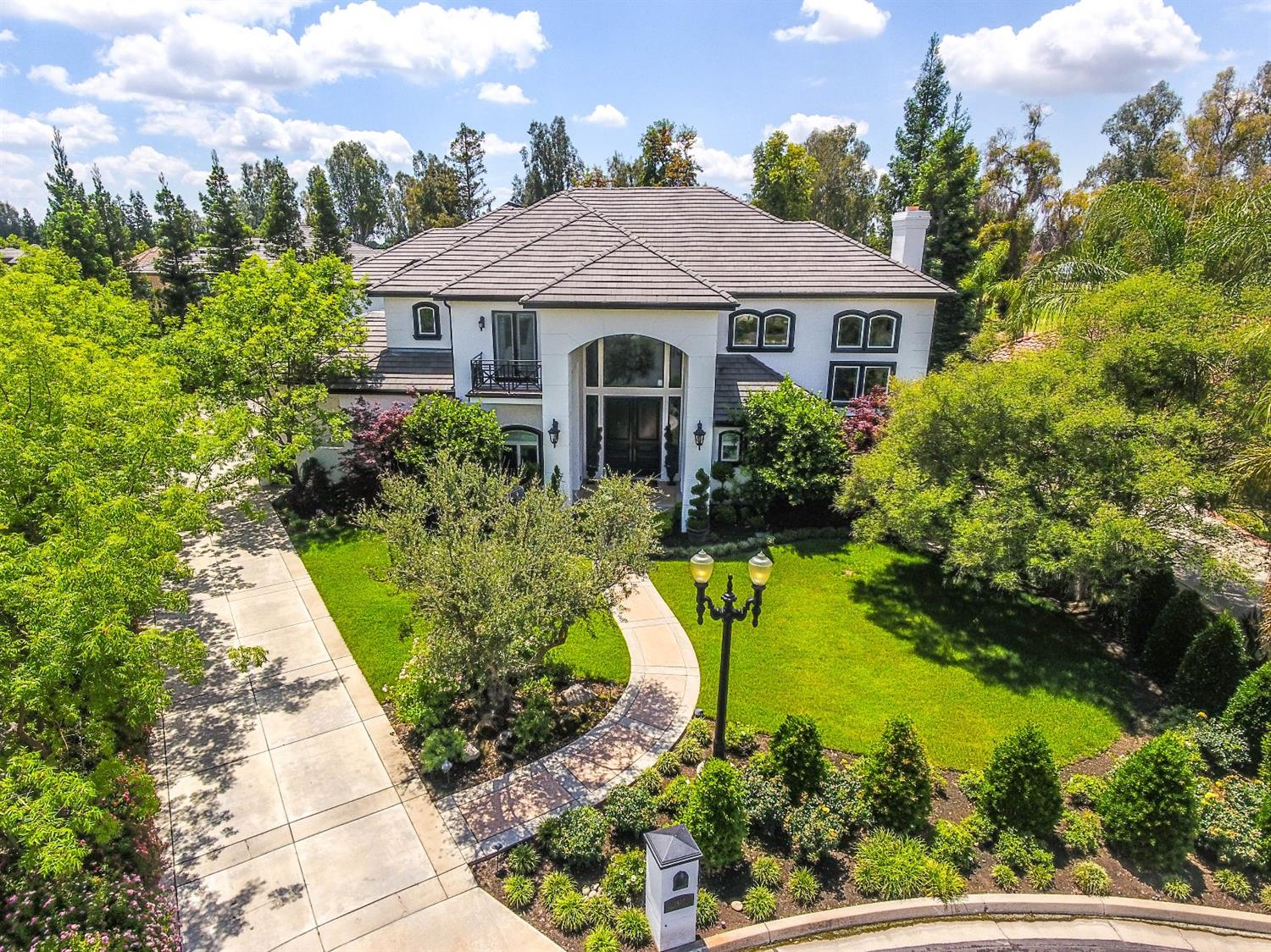 Luxury Estate on The Fairway at Fort Washington Country Club! This privately gated premier view lot at Country Club Estates II is masterfully remodeled to become one of Fresno's finest Estates. Gorgeous handcrafted home features impressive Great Room w/ Golf Course Views through bayed windows, Massive Hand Cast Stone Fireplace adorned by custom cabinetry, travertine floors, soaring box ceiling & wet bar w/ seating. Exquisite Kitchen will Impress! 48'' Dacor commercial range w/ 2 ovens, 2 dishwashers, warming oven, built-in cutting board, 2 sinks, 2 refrigerators, lrg pantry, & Breakfast Area. Relax in the Sumptuous Owners Retreat w/its two-sided fireplace, corner-sitting area w/ magnificent views, French doors to private balcony & Stunning Bath. Manicured yard features gorgeous panoramas w/ Pebbletec Pool & Spa, multiple patios, outdoor Kitchen & koi pond. Exquisite Finishes & Custom Refinements have been Flawlessly Employed Throughout. Luxury Properties of this Statue are a RARE find!