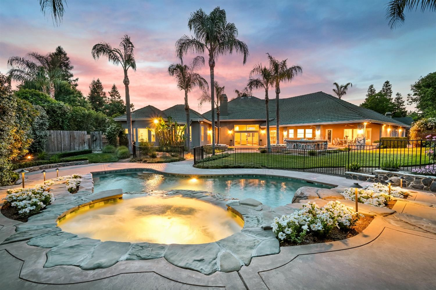The grand front entry is followed by the great room and breathtaking view of the spa and pool. In the backyard you hear the waterfall and see beautiful lighting on palm trees and walkways - private resort feel including built-in BBQ, covered patio, sound system and plenty of room for guests. This one-story open floorplan home with unique ceiling treatments and two fireplaces has a kitchen with large center island, dual dishwashers, walk-in pantry and custom bar with refrigerator making an entertainer's dream. The Family room and Library/Office have built-in shelves and cabinets. This custom home was built with tons of storage. Spacious Master bedroom with newly remodeled bathroom, dual sinks and shower heads, rain shower, tub and large walk-in closet. Bedrooms features include en-suite bathrooms, walk-in closets and back patio access. Single car garage has storage and built-in-shelving. Two-car garage has a workshop and more storage with built-in shelving. Custom black iron pool fence.