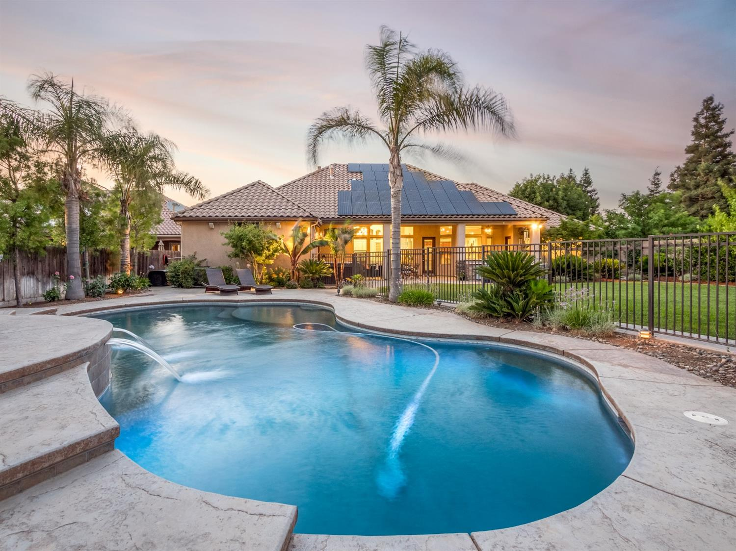 Set on a sprawling 18,800 sqft lot in Fig Garden Estates, one of Fresno's most prestigious neighborhoods, you will find serenity redefined. Tucked in behind your wrought-iron gate is a cutting-edge courtyard modern paradise built by Image Homes Inc. w/the world's finest appointments: 5 bedrooms, 3 bathrooms, 3,631 sqft. w/62 solar panels of owned solar. Experience the pinnacle of sophistication & modern design w/quality finishes throughout from your chef inspired kitchen with stainless-steel Kitchen-Aid pro appliances, double oven, custom cabinetry for your wine collection & built in cooler and ice maker. Entertain all summers in your spacious backyard and lounge by your Pebble Tec Pool with waterfall features & dining space. Start the outdoor built in bbq grill for a large outdoor dinner parties. This lovely home also has multiple fruit trees & over 10 feet of garden area. Why settle for anything less than the absolute best? Welcome home.