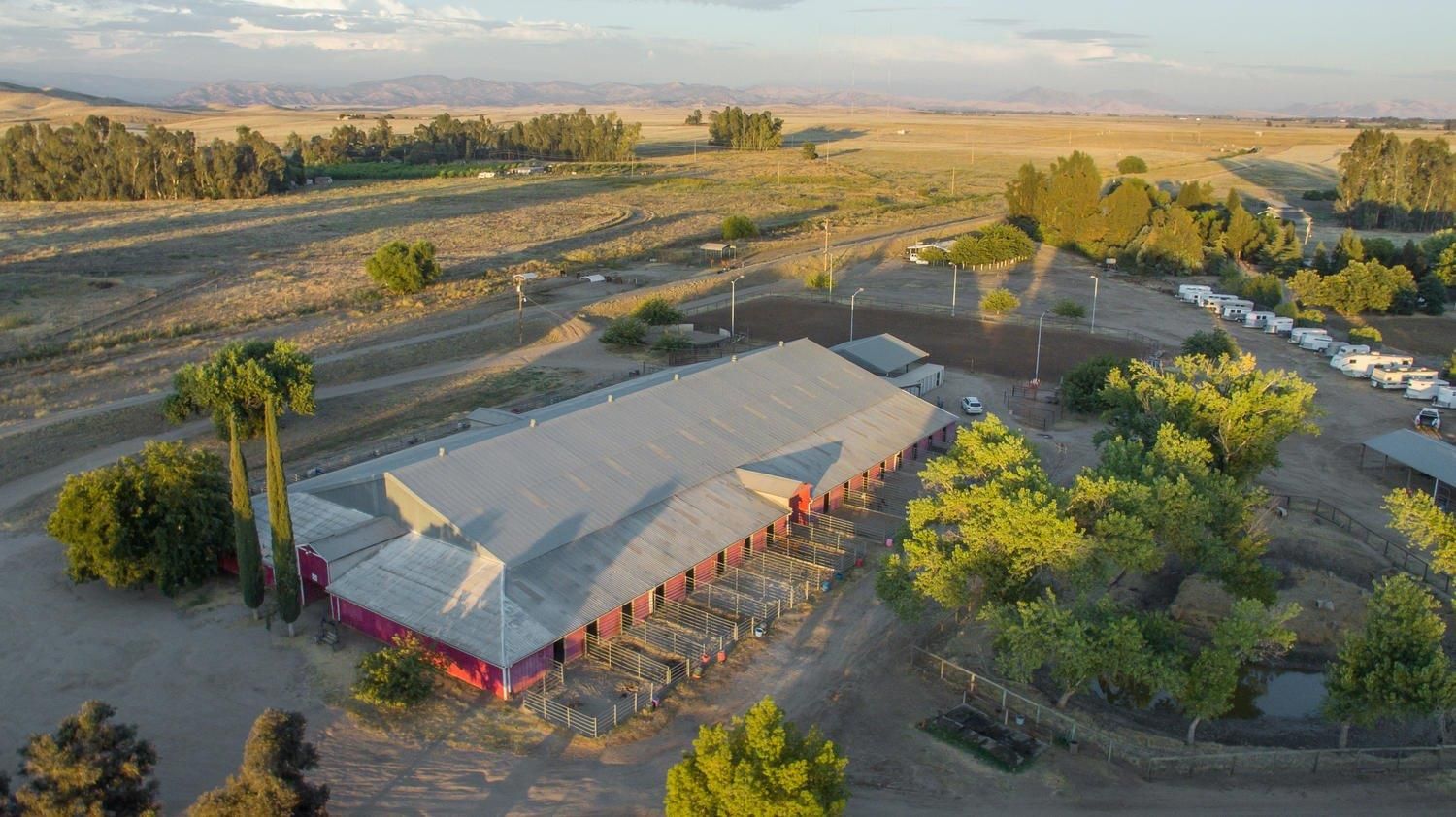 Exclusive Opportunity Fresno/Clovis fully licensed and permitted Equestrian Event and Boarding Facility. Licensed for 100 horses and permitted for events. This 12.5 acre property supports (1) The main barn 132'x228', total of 28 stalls/paddock 12' x 12' with 12' x 24' paddocks and 6 stalls 12' x 12' with 24' x 24' paddocks, concrete walls, self watering, feed manger, and rubber mats floors. 32 individual lockable tack rooms and grooming areas. The under roof arena is fully lighted and over head sprinklers, arena measures 79'x204'. (2) 2 long barns 29'x190'. (3) Feed barn 40'x40' (4) Fenced Round Pen 50', (5) Fenced dry pastures with shaded areas, cross ties/ wash rack. (6) Outdoor arena 120'x240' with stadium lighting. (7) Parking for horse trailers and outdoor lockers for tack. (9) 1942 + sq-ft 3/2 home sits on the front of the property.